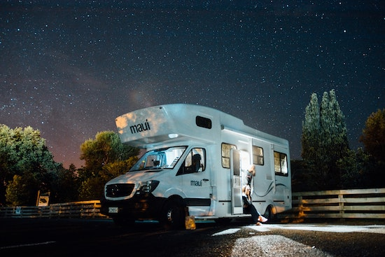 A RV at night with lights on and a family, perfect for a RV solar panel kit