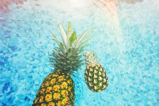 A pool with two pineapples heated by one of the best solar pool covers