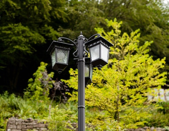 The best solar post lights on a traditional-style lamp post with greenery in the background