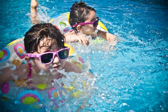 Kids swimming in a pool which is heated with the best solar pool heater