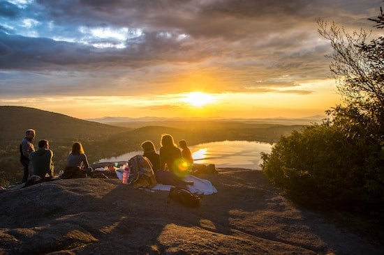 6 friends sitting on a mountain top with a solar powered generator providing power